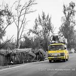 An overloaded yellow taxi brousse (Mazda Bongo) on the coastal road near Ifaty, Madagascar