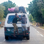 Two men hanging onto the back of an overloaded taxi brousse (Mazda Bongo) on the coastal road near Ifaty, Madagascar